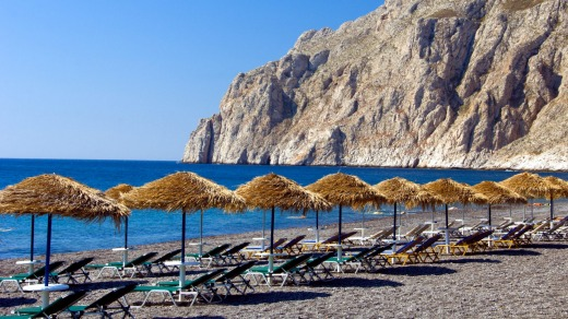 The black sand beaches with umbrellas and lounge chairs in Kamari on the Greek Island of Santorini.