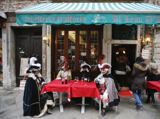 Masked people enjoy a drink in Venice, Italy.
