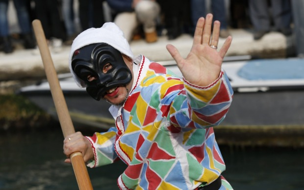 A man dressed as Arlecchino (Harlequin) waves as he rows a boat during the water parade, part of the Venice Carnival, in ...
