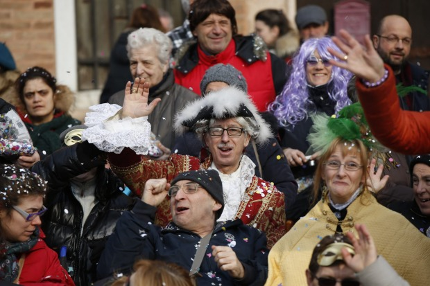 Spectators enjoy the water parade, part of the Venice Carnival, in Venice, Italy. The Venice carnival in the historical ...