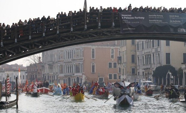 Boats sail under the Accademia Bridge during the water parade, part of the Venice Carnival, in Venice, Italy. The Venice ...