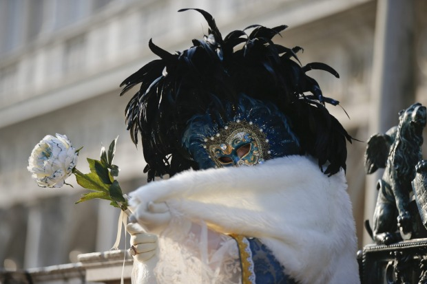 A masked woman poses in St. Mark's square during the Venice Carnival. The Venice carnival in the historical lagoon city ...