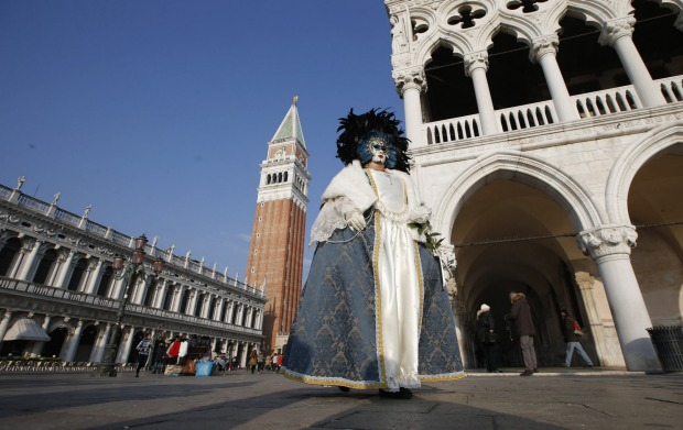 A masked woman walks in St. Mark's square during the Venice Carnival, in Venice, Italy. The Venice carnival in the ...