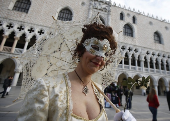 A masked woman walks prior to the Carnival Grand Opening show, in Venice, Italy. The Venice carnival in the historical ...