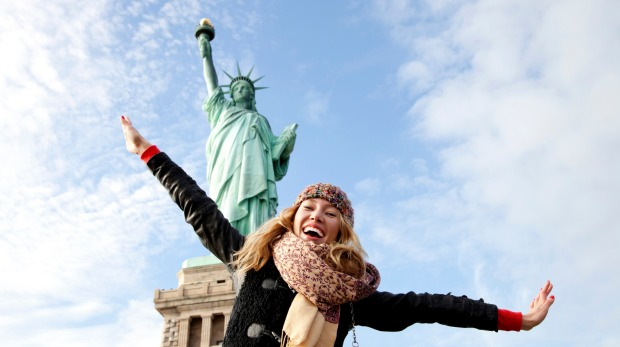 A beautiful young blonde woman  at The Statue of Liberty in New York.