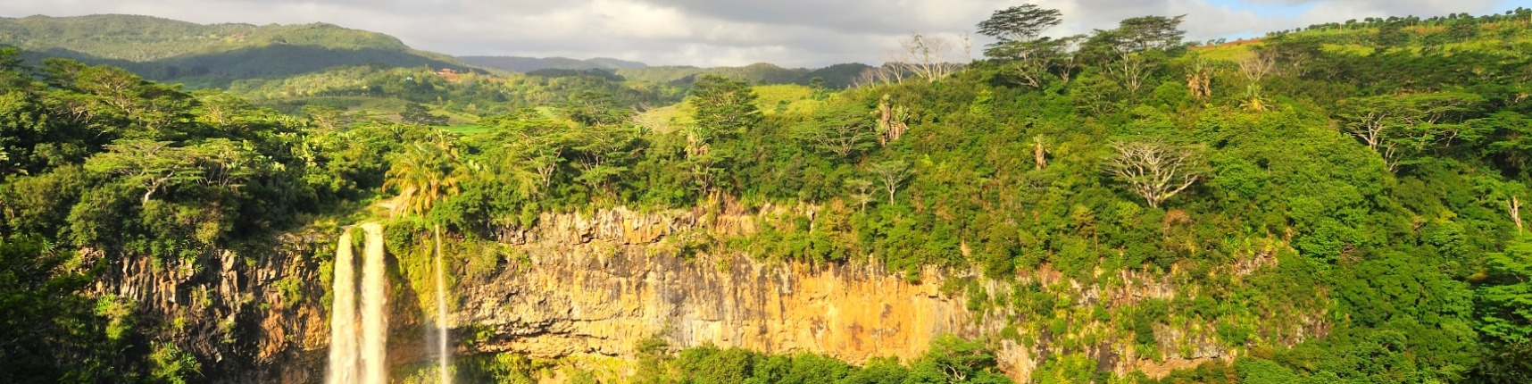 The Chamarel waterfall in Mauritius in late afternoon with the sun cutting across the gorge and the seemingly infinite ...
