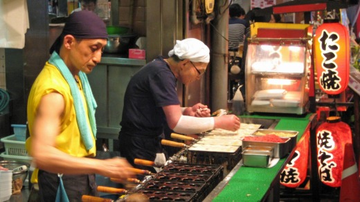 Osaka street vendors preparing fried octopus balls (takoyaki).