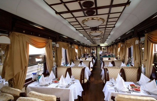 Dinner service in the Restaurant Car on a Golden Eagle luxury train.
