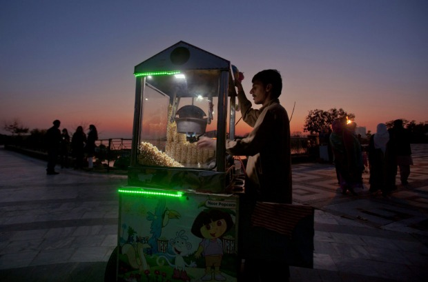 A popcorn seller waits for customers at Lake View Park on the outskirts of Islamabad, Pakistan.