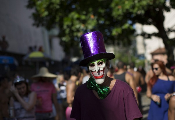 """A reveller wearing a mask depicting the """"The Joker"""" comic character, attends the """"Carmelitas"""" block party during ..."""