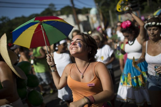 """A reveler holds up a colored umbrella as she dances at the """"Carmelitas"""" block party during Carnival celebrations in Rio ..."""