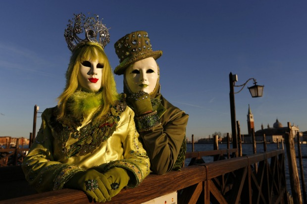 Two costumed revellers wearing volto masks at St Marks Square during Venice Carnival.