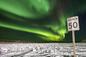 The northern lights illuminate the night sky above a road sign in Inuvik, Northwest Territories, Canada.