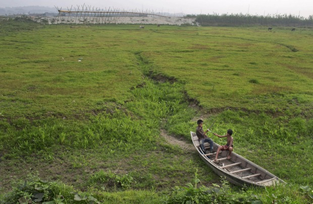 Bangladeshi children play on an abandoned boat, on the dried bed of a lake that used to be linked to the River Turag in ...