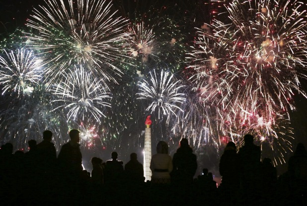 North Koreans watch from the Kim Il Sung Square as fireworks explode over the Juche Tower during celebrations of the ...