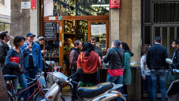 Bodega patrons spill out into the street in Barcelona, in Spain.