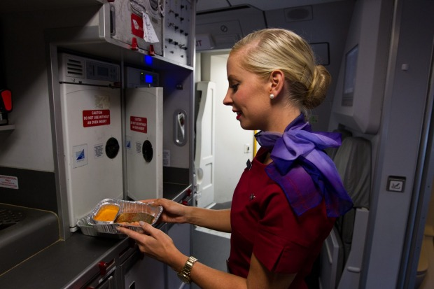 A Virgin Australia flight attendant prepares trout to serve to business class passengers.