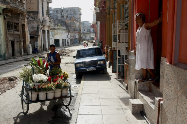 A flower salesman pushes his cart down a street in Havana, Cuba.