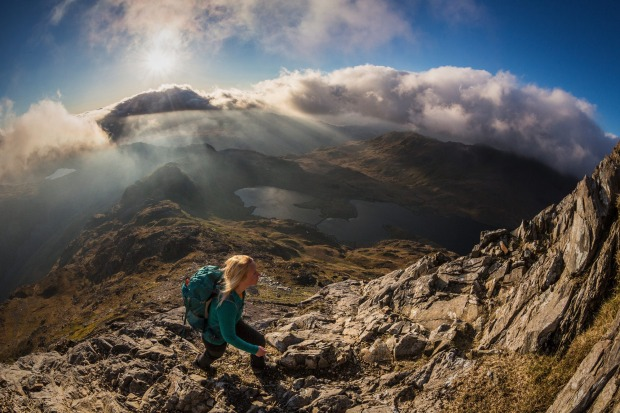 A young woman walking on the rocky slopes of Crib Goch, and the view of the Llyn Llydaw lake and valley through low cloud.