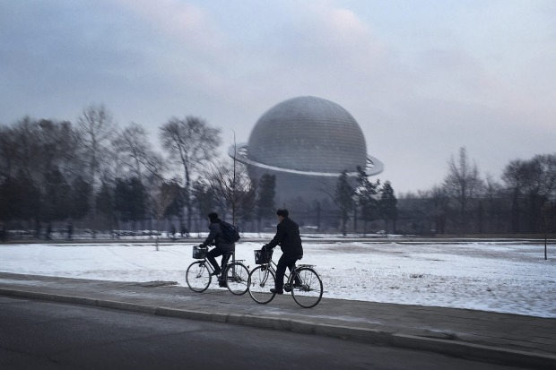 North Koreans cycle past a planetarium at the Three Revolutions Exhibition Hall in Pyongyang, North Korea.