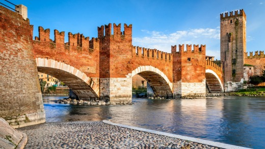 The Adige River in Verona with medieval landmarks Ponte Scaligero and Castelvecchio.