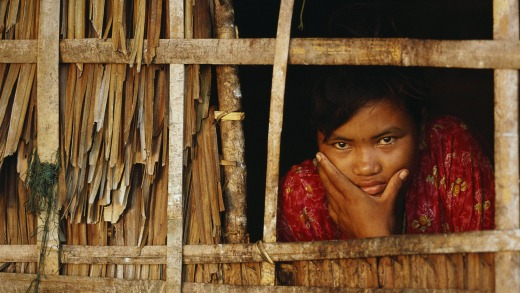 A Moken woman looks out from inside her home, Myanmar.