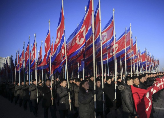 North Koreans parade with the North Korean flag in Kim Il Sung Square in Pyongyang, North Korea, in February 2016, to ...