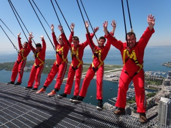 A group teetering over the edge of a skyscraper during a CN Tower Edgewalk.