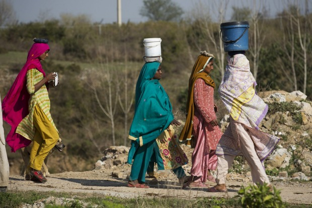 Pakistani women fetch clean water for their families in the suburbs of Islamabad, Pakistan.
