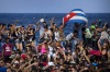 Fans dance on Havana's seafront during a free concert by the US electronic music group Major Lazer in Havana, Cuba.