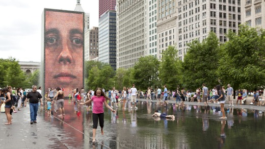 Children play in water of the Crown Fountain in Millennium Park in downtown Chicago.