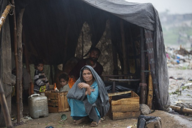 Members of a Pakistani nomadic family sit in their makeshift home during a rainstorm in Islamabad, Pakistan.