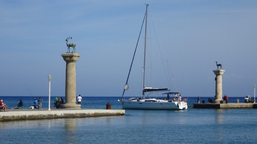 A yacht passes through the old harbour entrance where the Colossus of Rhodes once stood.
