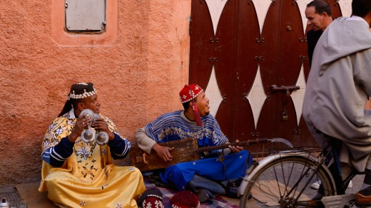 Gnawa street musicians playing hajhuj and krakeb in Marrakech talking to a passerby.