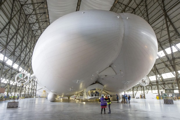 Workers and media stand under the front of the hull of the Airlander 10 in Bedford, Britain.