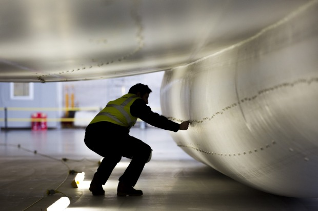 A worker inspects the skin of the hull of the Airlander 10.