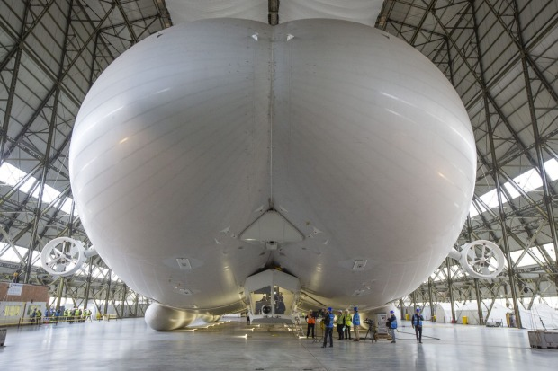 Workers and media stand under the front of the hull of the Airlander 10 hybrid airship during the global media launch ...