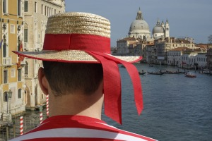 A gondolier surveys the Venice cityscape.