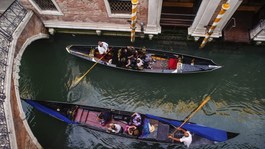 Gondoliers in a canal, Venice, Italy.