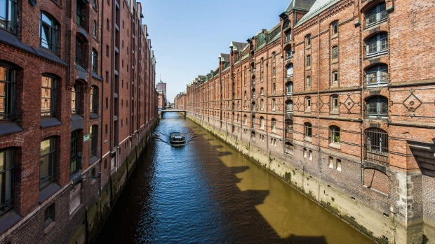 A tour boat passes along a canal in the Speicherstadt district of Hamburg, Germany.
