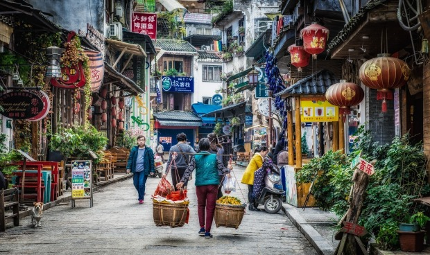 Even in modern day Yangshuo, China, the ancient ways are the most efficient. Here a lady is moving a huge basket of ...