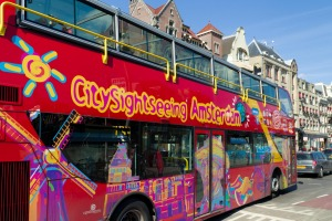 An Amsterdam sightseeing tourist bus with a panoramic roof offers tourists a hop-on, hop-off service at 12 points of ...