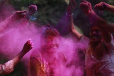 People smear colored powder on the face of a girl during celebrations marking Holi, the Hindu festival of colors, in ...