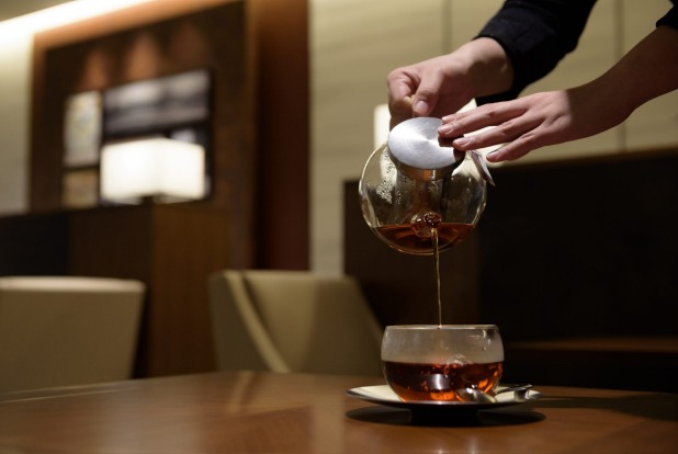 An employee serves tea to a customer at the View Gold Lounge, operated by East Japan Railway Company and View Card, at ...