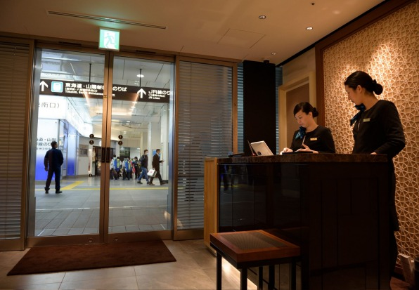 Employees stand at a reception counter of the View Gold Lounge, operated by East Japan Railway Company and View Card, at ...