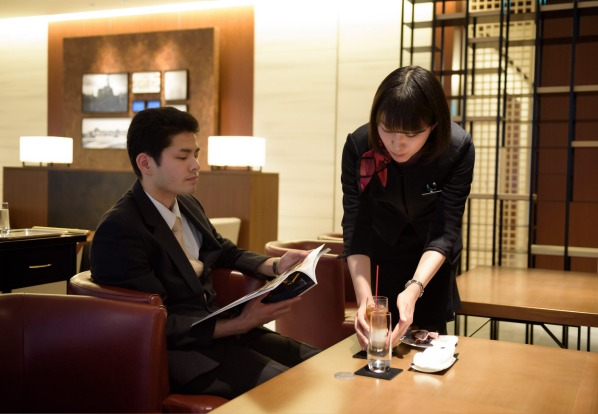An employee serves a drink to a customer in the View Gold Lounge, operated by East Japan Railway Company and View Card, ...