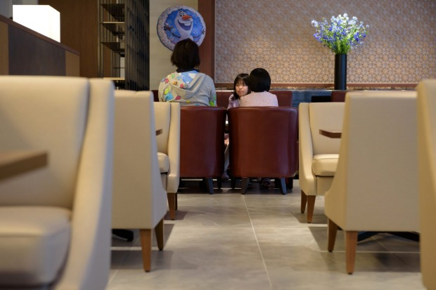 A woman and her daughters relax in the View Gold Lounge, operated by East Japan Railway Company and View Card, at Tokyo ...