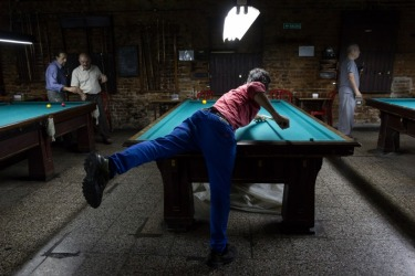 A man practices at a traditional billiard hall in Buenos Aires, Argentina. We came across this billiard hall while on a ...