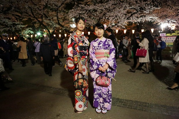 These ladies pose for portraits under the cherry blossoms trees at Ueno park in Tokyo, Japan.  During cherry blossom ...