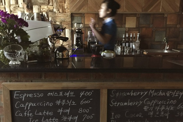 A waitress works behind the counter at the Kumrung cafe where the menu includes the usual favourites of customers in the ...